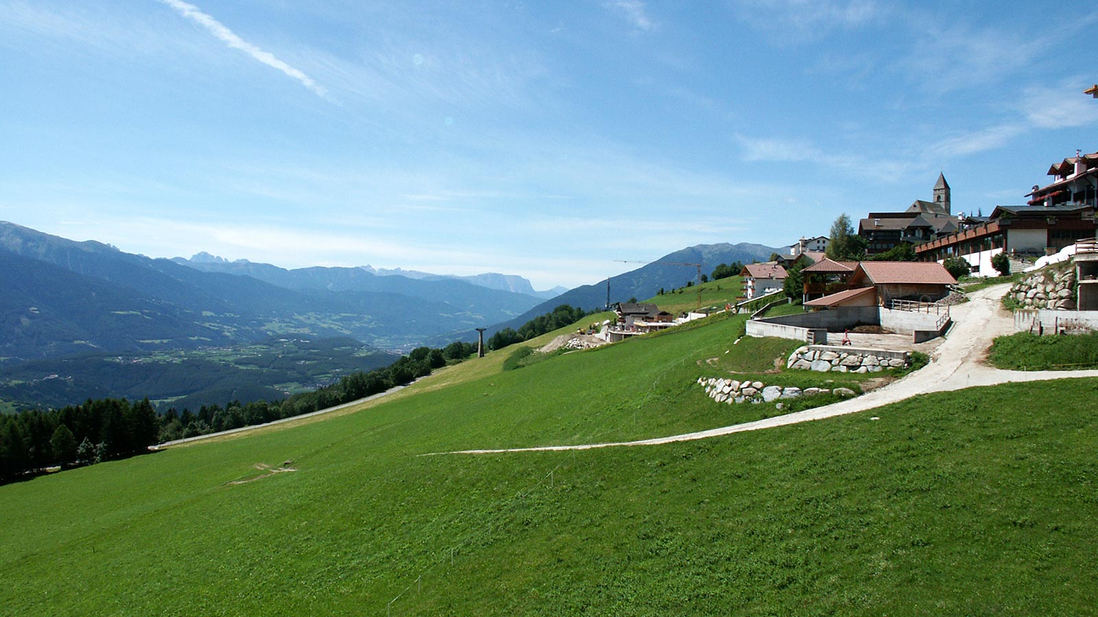 Panoramic view of Maranza during summer with green meadow and view of the valley below