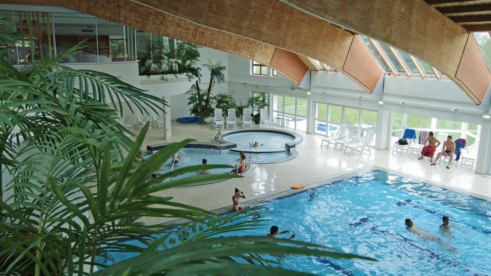 View from above at the swimming pools in the indoor pool Alpinpool in Maranza with guests in the water