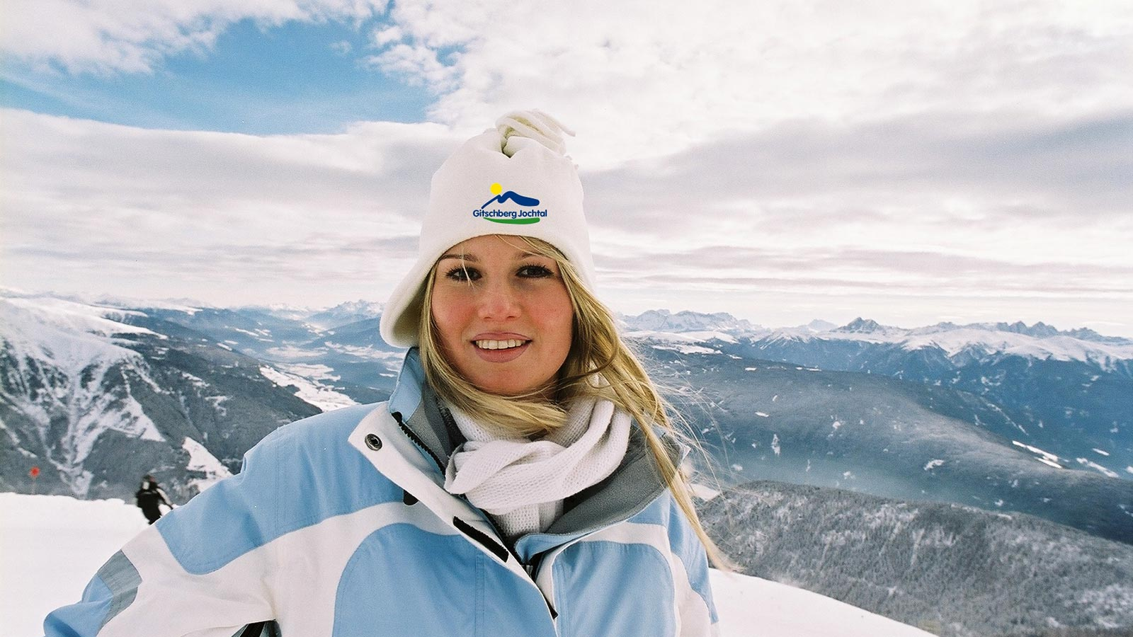 Woman with blonde hair with a beanie with the Gitschberg-Jochtal logo, snowy landscape in the background