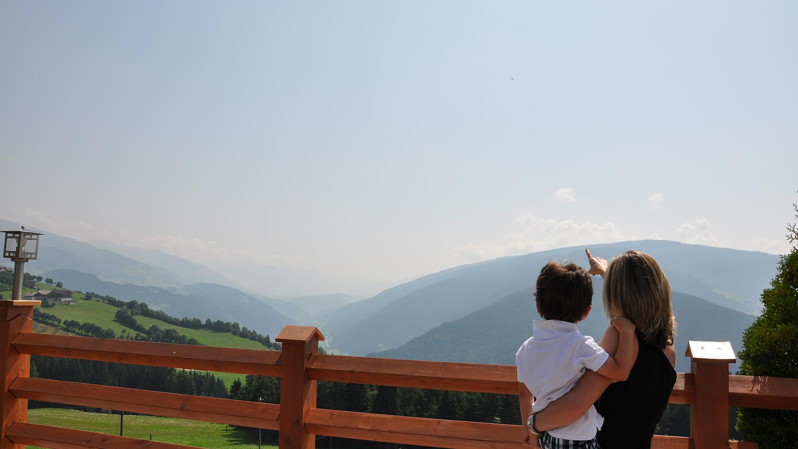 A mother with her son in the arm looking at the landscape of Maranza from the terrace of the Wiesenrain