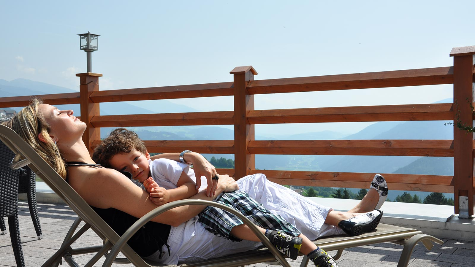 A mother relaxing on a deckchair on the terrace of the Wiesenrain with the son hugging her on a sunny day