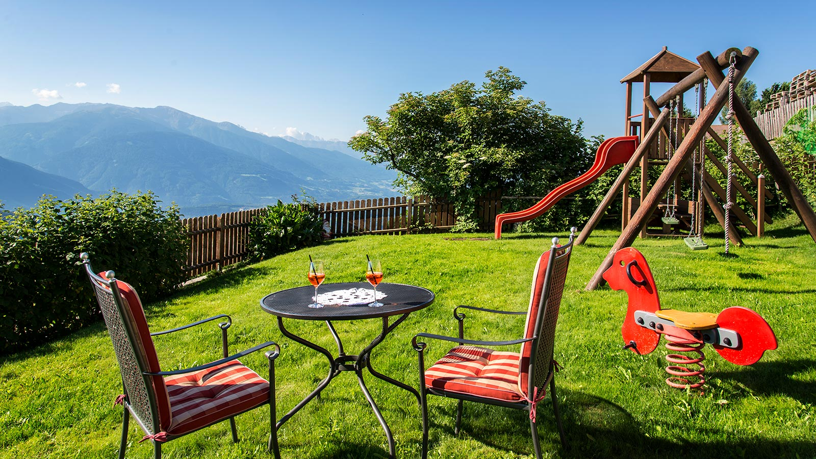 The garden of the Pension Wiesenrain with a table and two aperitifs with the beautiful view of the mountains